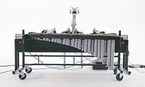 The musical robot Shimon sitting in front of a marimba.